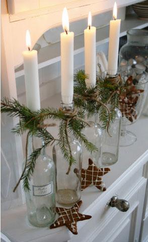 Portavelas navideño hecho con una botella de vidrio transparente, una rama de abeto y un nudo de hilo de cáñamo.