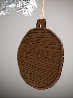 Bola de Navidad hecha con cartón ondulado y decorada con un bolígrafo negro para enganchar en un árbol de Navidad blanco o plateado.