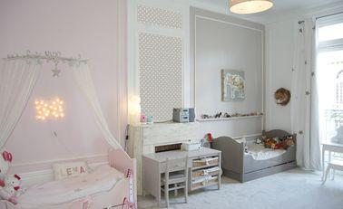 Para delinear el lado de niña y el lado de niño, el papel tapiz de lunares hace una transición suave desde el dormitorio de la princesa rosa al espacio de niño gris ratón.
