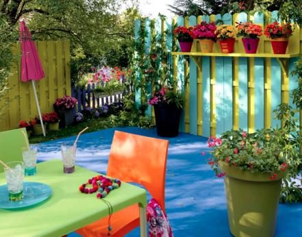 Decoración de balcón muebles de jardín verde y naranja sobre suelo exterior azul brillante, empalizada de madera y frascos de colores brillantes