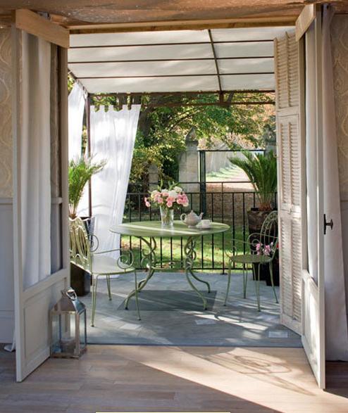 Instalación de una íntima terraza decorativa en la ampliación del salón con techo de cristal y cortinas de aire que cuelgan de la estructura de hierro forjado.