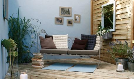 Ampliación de salón con terraza de madera y muebles de jardín de hierro forjado.