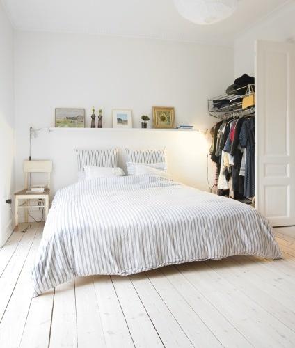 Decoración dormitorio adulto con paredes, parquet y cabecero blanco.  La funda nórdica de algodón a rayas grises y blancas completa la armonía de los colores decorativos.