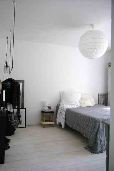Una decoración de dormitorio escandinava disponible en blanco, gris y negro.  Pintura de pared blanca mate, funda de cama de algodón gris, negro se trae con el armario colgado en el perchero
