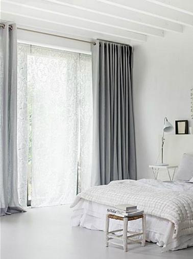 Decoración de dormitorio gris y blanco en la que el único toque de gris lo aporta el color gris ratón de las cortinas dobles.  sobre la cama blanca, un pequeño marco negro.  Estribo, taburete de madera