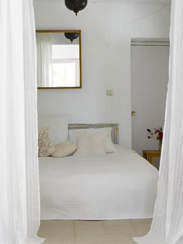 Color de dormitorio beige y blanco.  Pintura blanca mate, puerta pintada beige.  Cabecero de madera clara, suelo de gres beige, cojines de marfil, cortinas de velo de color blanquecino claro.