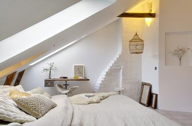 Un dormitorio beige y blanco acondicionado en un antiguo taller de artesanos.  Para construir una decoración refinada, las paredes encaladas enfatizan las vigas del techo, la ropa de cama beige refuerza la suavidad del ambiente.