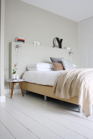 Dormitorio beige y blanco para un ambiente zen.  El cabecero original está realizado con un encofrado mediano y está pintado del mismo color beige lino que la pintura de la pared.  suelo de parquet pintado de blanco, manta de cama de mohair beige