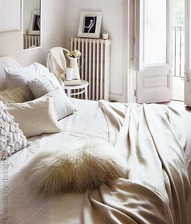 Decoración de dormitorio de adultos en beige y blanco para un ambiente envolvente y femenino.  Mezcla de tejidos sedosos y pieles para cojines y ropa de cama en tonos beige y blanco.