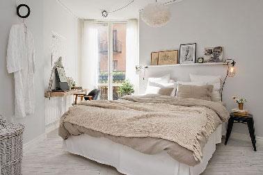 El beige y el lino se convierten en colores cómplices en este dormitorio blanco, que se impone suavemente sobre los complementos decorativos y la ropa de cama.  Un taburete de madera sirve como mesita de noche, una vieja mesa cortada por la mitad y repintada en blanco se transforma en una consola de escritorio.  Un juego de colores suaves y brillantes para una decoración de habitación chic bohemia.
