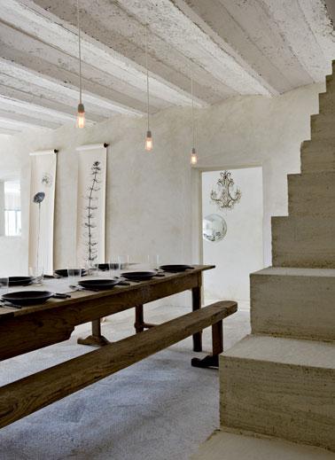 En las paredes del comedor se recubren con cera espesa la tierra vieja de una casa decorativa.  Vigas encaladas y escalera de madera blanca.