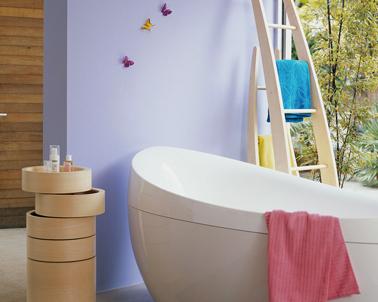 Decoración de baño contemporánea.  Alrededor de la bañera de diseño, una pintura de pared de color lila completada con toques de colores vivos con las toallas de baño rosa, azul y amarillo