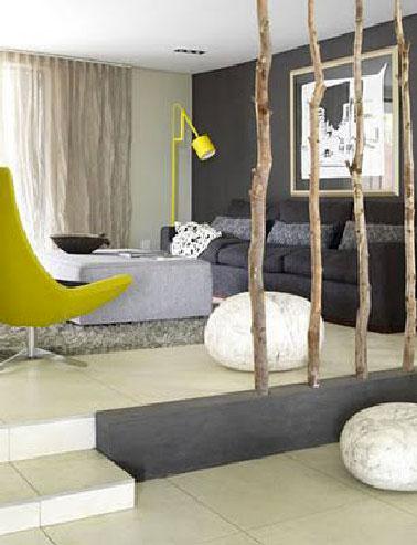 Una separación del espacio de la sala de estar del comedor construido con árboles pequeños fijados y sellados en un cofre de madera pintado en taupe para recordar el color de la pared de la sala de estar y el sofá.