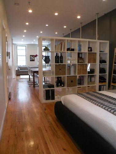 En un estudio, la separación de la habitación individual con una estantería abierta aísla el área del dormitorio mientras retiene la luz proveniente de la sala de estar.