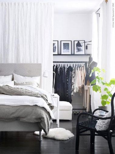 En un dormitorio con vestidor abierto, una cortina de velo blanco sirve como separación luminosa y estética
