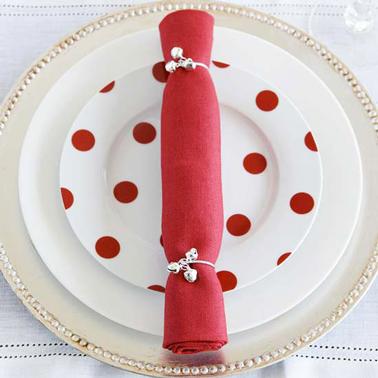 ¡Una servilleta plegable ultra simple de hacer y que tendrá su efecto sobre un plato rojo y blanco!  La toalla roja se dobla en un rollo y se cierra con dos cordones plateados.