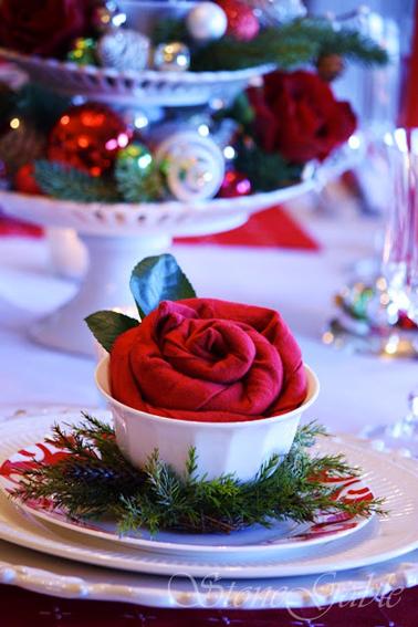 Servilleta roja doblada en forma de flor colocada en una taza blanca y decorada con follaje verde
