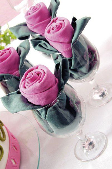 Un plegado en forma de capullo de rosa realizado con dos servilletas presentadas en copa de vino
