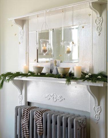 Decoración navideña para el rincón del radiador del salón con ramas de verdor, velas blancas y las tradicionales bolas navideñas plateadas.  En el radiador los calcetines esperan los regalos