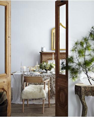 Sobre la mesa navideña de un comedor decorado zen, manteles en capas de lino y algodón mezclando mantel blanco y lino decorado con velas blancas y ramas para darle un toque de color