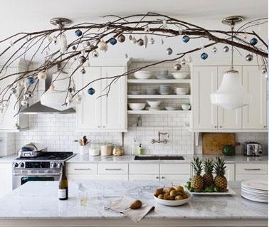 Una hermosa decoración de cocina blanca para Navidad, hecha con una gran rama de arbusto y adornos navideños dorados y plateados sobre la mesa de la cocina.