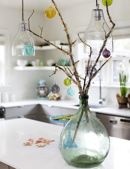 Una idea de decoración navideña fácil de hacer con un ramo de ramas y pequeñas bolas navideñas multicolores para poner en la mesa del comedor o de la cocina