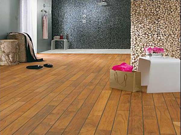 En el gran baño, el suelo de teca marrón oscuro resalta la ducha italiana en mosaicos negros y combina con la decoración natural.