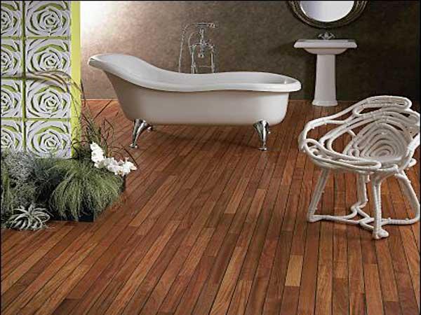 Suelos de baño de madera africana exótica Doussie.  Sus colores naranja-marrón contrastan con la moderna bañera y el lavabo blanco.