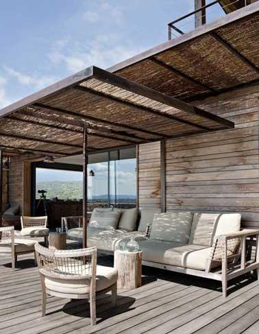 Una pérgola canisse da sombra a una terraza de madera de una casa corsa.  El mobiliario de jardín de teca contemporáneo y confortable con sus grandes y gruesos cojines le invita a relajarse.