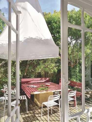 Enclavada en medio de la vegetación, esta terraza da la bienvenida a toda la familia alrededor de su gran mesa de madera.  La vela de sombra y el suelo de madera subrayan su facilidad de uso