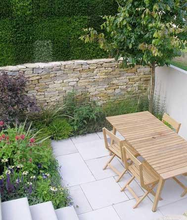 Suelo de losa de hormigón moderno y muro de valla de piedra para la pequeña terraza de una masía provenzal.  Aislada sin estar cerrada, recibe a sus invitados alrededor de una mesa de madera