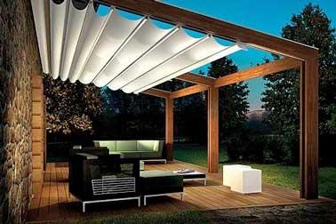 Disposición de una terraza de diseño con muebles de jardín contemporáneos y una pérgola retráctil sobre una estructura de marco de madera y aluminio.  Iluminado por una lámpara de cubo al aire libre