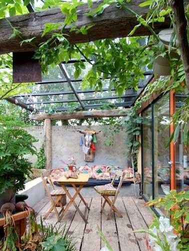 El techo de vidrio y las enredaderas crean la atmósfera de cobertizo de esta terraza.  Amueblado con muebles de jardín y materiales reciclados, su encanto es único