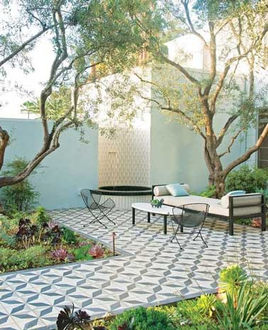 Ejemplo de distribución de terraza con revestimiento de baldosas de cemento azul y blanco.  Sobrios y auténticos, armonizan con el color azul pastel de la valla del jardín.