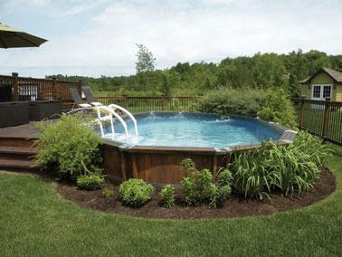 Un magnífico escenario para descansar en esta terraza de madera rodeada de césped y acondicionada con una piscina sobre rasante donde se invita a la vegetación.