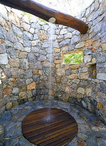 ducha de jardín para una atmósfera provenzal instalada en una gran viga de madera en un espacio construido en piedras