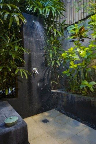 Ducha de jardín instalada en un remanso de vegetación y piedras negras.  En el suelo, un mosaico de grandes baldosas de piedra beige.