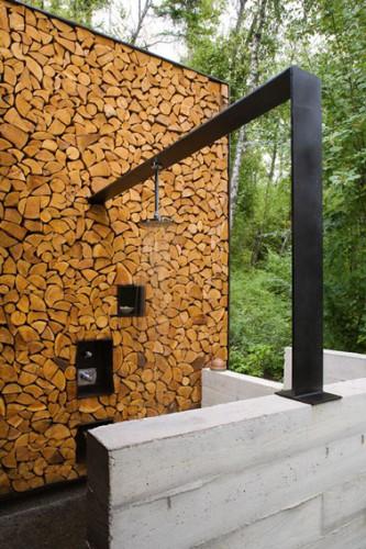 Ducha de jardín instalada sobre una viga metálica en L que se apoya en una pared montada con troncos de madera.