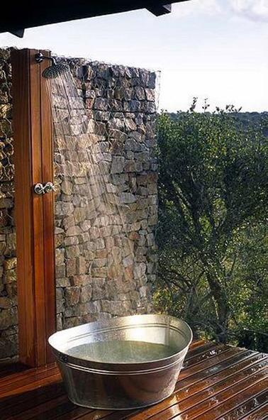 Ducha exterior de madera instalada en la pared de la casa, a modo de plato de ducha, gran lavabo de aluminio colocado sobre suelo de teca