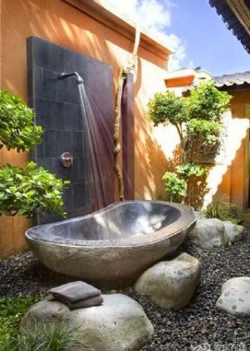 Una ducha exterior con bañera de piedra para plato de ducha instalado en un ambiente con colores mágicos y un suelo de grandes cantos rodados.