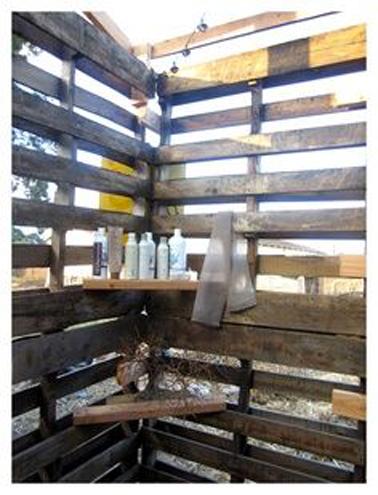 ducha al aire libre instalada en una pared perimetral construida con paletas de madera recuperada y dos estantes pequeños para colgar productos de ducha y toallas