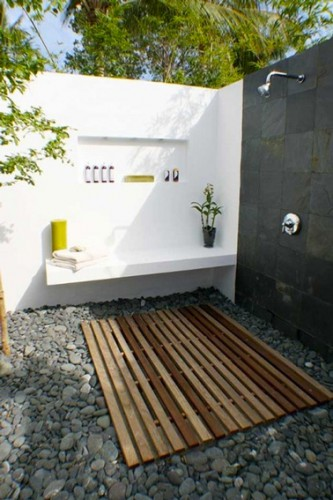 ducha de jardín instalada en dos paredes circundantes pintadas en blanco y gris antracita.  en una de las paredes un pequeño banco de hormigón.  En el suelo, un suelo de rejilla de teca