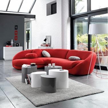 Este sofá de esquina redondeado rojo ilumina la decoración de esta sala de estar de diseño en blanco y negro.  Original aporta prestigio y modernidad a la sala de estar.