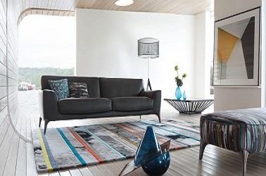 En este salón con muebles de diseño, el sofá de cuero negro combina con la alfombra de lana étnica, la mesa de centro de diseño y el reposapiés revestido con un tejido estampado que hace eco de los colores de la alfombra.