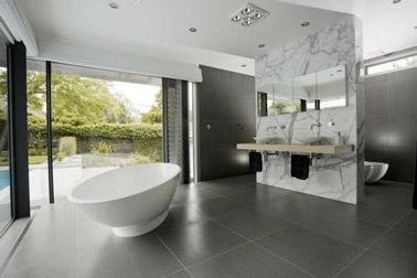 Con azulejos gris antracita y un delimitador de aspecto mármol, ¡este baño tiene todo diseño!  Una decoración resaltada por una bañera independiente, ¡eso es genial!