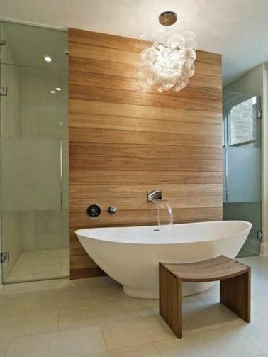 Como una pequeña zona de spa relajante, esta bañera ovalada independiente encuentra su lugar en el baño de madera y lo sublima para momentos de tranquilidad.