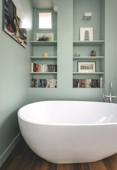 Suavidad y sencillez van de la mano en este pequeño cuarto de baño con paredes de color verde pastel y suelo de parquet equipado con una bañera independiente y una estantería.