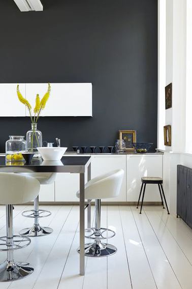 En una de las paredes de una cocina blanca de estilo moderno, una pintura gris carbón es una buena manera de energizar la atmósfera mediante el uso de contrastes.