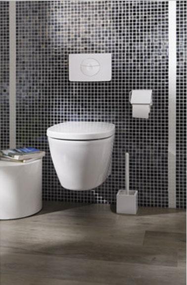 Inodoro blanco suspendido de diseño, forma redondeada, en la pared 5X5 azulejos negros, juntas blancas, suelo de parquet flotante