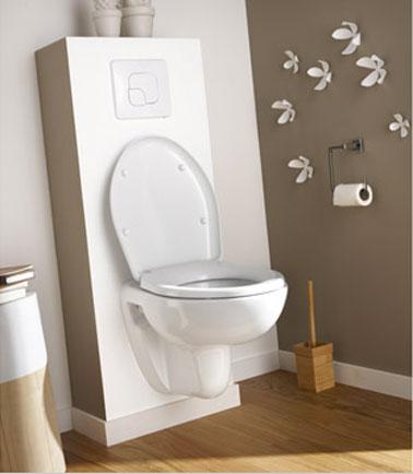 Inodoro clásico suspendido, encofrado de bloques a la vista pintado de blanco, paredes pintadas de color topo.  Suelo de parquet de bambú